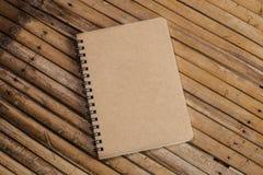 Cuaderno cerrado de Brown en un fondo de bambú, textura simple Imágenes de archivo libres de regalías