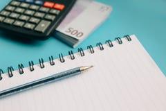 cuaderno claro, pluma, paquete de billetes de banco euro y una calculadora en un fondo azul fotografía de archivo
