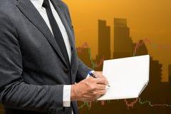 Cuaderno comercial del control del hombre de negocios y línea comercial gráficos de las divisas Fotos de archivo libres de regalías