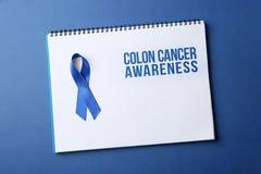 Cuaderno con conciencia del cáncer de colon de la cinta azul y del texto imagen de archivo