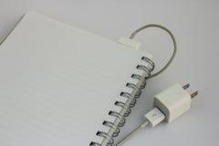 Cuaderno con el cargador de batería Imagen de archivo libre de regalías