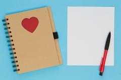 Cuaderno con el corazón y la hoja de papel en blanco en la tabla Fotos de archivo libres de regalías