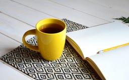 Cuaderno con el lápiz amarillo y helecho en el fondo blanco fotos de archivo