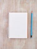 Cuaderno con el lápiz en el escritorio Foto de archivo