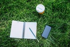 Cuaderno con el lápiz, smartphone con la pantalla en blanco y taza de café disponible en césped verde imagenes de archivo
