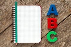 Cuaderno con el lápiz y las letras de ABC Foto de archivo