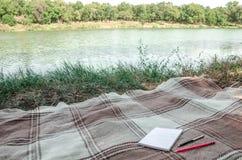 Cuaderno con el lápiz y notas sobre hierba verde del espacio en endecha del plano Foto de archivo libre de regalías