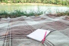 Cuaderno con el lápiz y notas sobre hierba verde del espacio en endecha del plano Imagenes de archivo