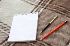 Cuaderno con el lápiz y notas sobre la sobrecama en endecha del plano Foto de archivo libre de regalías