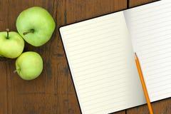 Cuaderno con el lápiz y manzanas en una tabla de madera Fotos de archivo libres de regalías