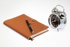 Cuaderno con el reloj Imagenes de archivo