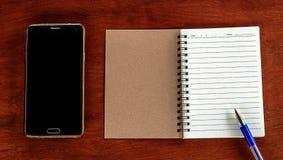 Cuaderno con el teléfono Fotografía de archivo