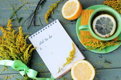 Cuaderno con el texto manuscrito, ramo de wildflowers amarillos adornados con la cinta de satén, manzana y taza de té con el limó Fotografía de archivo