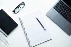 Cuaderno con la pluma en el fondo blanco Tabla de la oficina con el ordenador portátil, cuaderno, vidrios foto de archivo libre de regalías