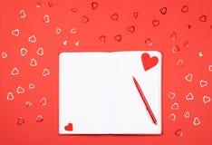 Cuaderno con la pluma en fondo rojo con confeti en forma de corazón fotografía de archivo