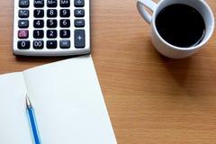 Cuaderno con la pluma, la calculadora y la taza de café blanca Imagenes de archivo