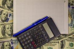 Cuaderno con la pluma y calculadora en los cientos billetes de dólar americanos Fotos de archivo