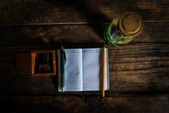 Cuaderno con la pluma y linterna vieja en el escritorio de madera viejo Visión superior Imagen de archivo