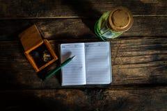 Cuaderno con la pluma y linterna vieja en el escritorio de madera viejo Visión superior Foto de archivo