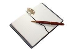 Cuaderno con la señal de madera de la pluma y del oro imágenes de archivo libres de regalías