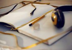 Cuaderno con la señal, el lápiz y los auriculares amarillos fotografía de archivo