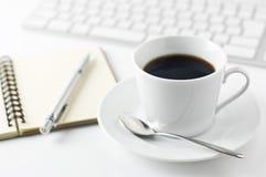 Cuaderno con la taza de café y de libreta con la pluma o Fotografía de archivo