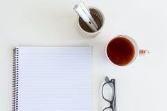 Cuaderno con la taza de té Fotos de archivo libres de regalías