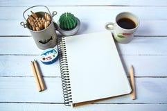 Cuaderno con la taza de tabla blanca de madera del café Imagenes de archivo