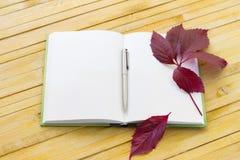 Cuaderno con las hojas de la pluma y de otoño Fotografía de archivo libre de regalías