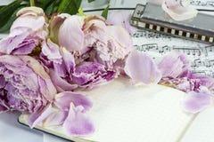 Cuaderno con las peonías y la armónica marchitadas foto de archivo