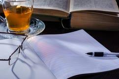 Cuaderno con los libros de trabajo al lado de una taza de té y de los vidrios en la madrugada foto de archivo libre de regalías