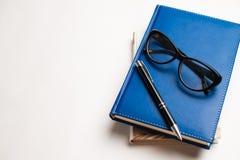 Cuaderno con los vidrios y la pluma, libro con los vidrios, cuaderno azul fotografía de archivo libre de regalías