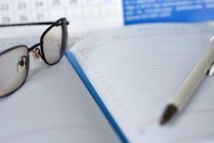 Cuaderno con un calendario para las notas sobre la mesa imagenes de archivo