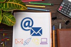 Cuaderno con un correo electrónico de las notas en la tabla de la oficina con las herramientas con imagen de archivo libre de regalías