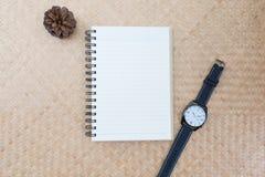 Cuaderno con un reloj en una estera Foto de archivo libre de regalías