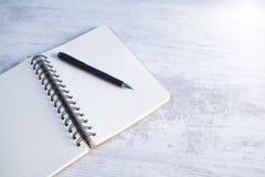 Cuaderno con una pluma en la mesa imagen de archivo