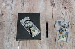 Cuaderno, dólares, lupa y pluma grises en una tabla de madera fotografía de archivo