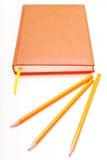 Cuaderno de Brown y pencisl amarillo en un fondo blanco Fotos de archivo