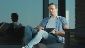Cuaderno de cierre del hombre de negocios casual Hombre moderno del primer que trabaja en el ordenador portátil almacen de video
