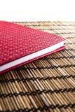 Cuaderno de cuero rojo en la estera de bambú Imagen de archivo