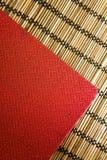 Cuaderno de cuero rojo en la estera de bambú Foto de archivo libre de regalías