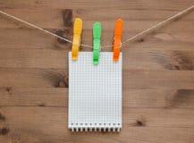 Cuaderno de la ejecución con las pinzas coloreadas en el fondo de madera Imagen de archivo libre de regalías