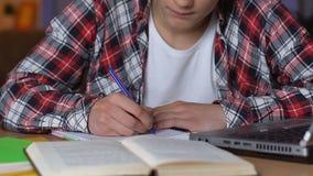 Cuaderno de la escritura del estudiante universitario, haciendo ejercicio de la preparación, conocimiento de la escuela almacen de metraje de vídeo