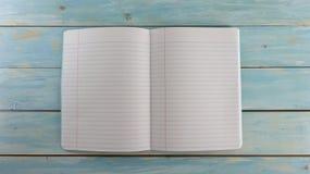 Cuaderno de la escuela en el fondo de madera azul del tablero - bandera de la educación imagen de archivo