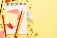 Cuaderno de la escuela y diversos efectos de escritorio sobre el escritorio amarillo fotos de archivo