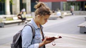 Cuaderno de la lectura de la mujer en campus del estudiante almacen de metraje de vídeo