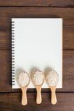 Cuaderno de la receta, arroz en cuchara de madera en fondo de madera Fotos de archivo
