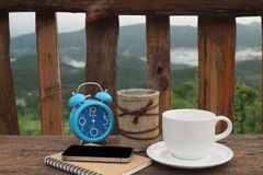 Cuaderno de la taza de café y del teléfono móvil en la tabla Foto de archivo libre de regalías