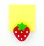 Cuaderno de notas amarillo con el clip de la fresa Fotos de archivo libres de regalías