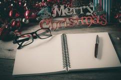 Cuaderno de notas con el lápiz en el saludo de madera de la feliz Navidad del concepto de los accesorios de escritorio a través d Fotos de archivo